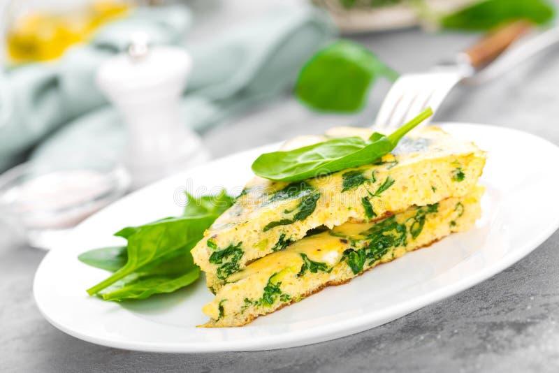 Omlet z szpinaków liśćmi Omelette na talerzu, rozdrapani jajka zdjęcie royalty free