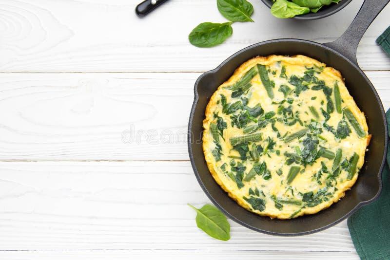 Omlet z szpinakami i fasolkami szparagowymi, zdrowy jedzenie Jajka i mleka Frittata, wyśmienicie śniadanie W czarnej smaży niecce obraz royalty free