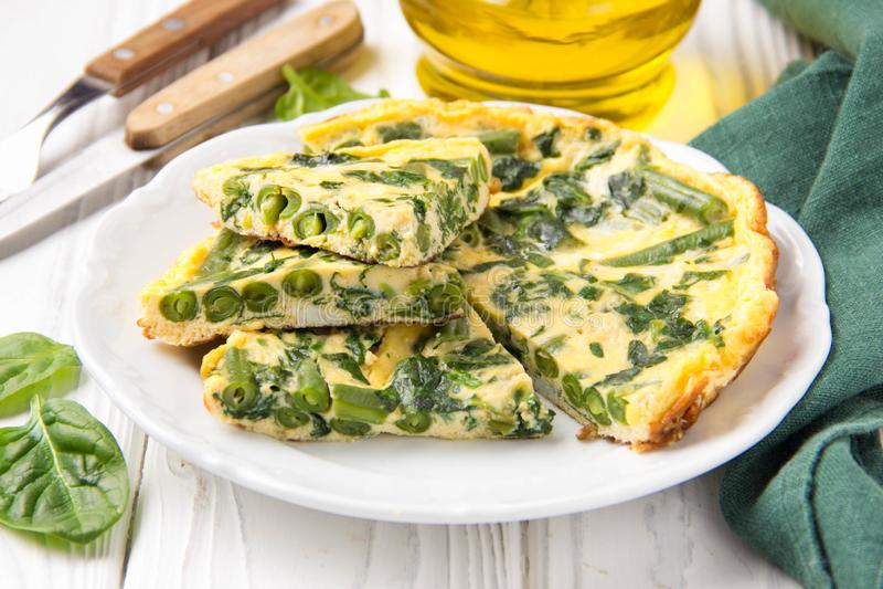 Omlet z szpinakami i fasolkami szparagowymi, zdrowy jedzenie Jajka i mleka Frittata, wy?mienicie ?niadanie na bia?ym drewnianym t obraz stock