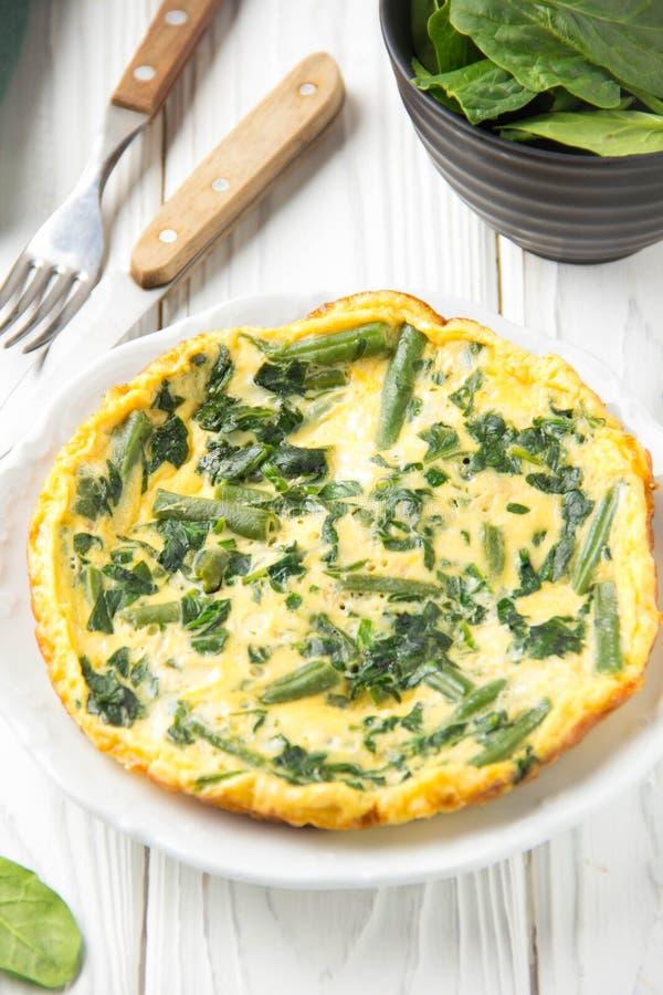 Omlet z szpinakami i fasolkami szparagowymi, zdrowy jedzenie Jajka i mleka Frittata, wy?mienicie ?niadanie na bia?ym drewnianym t obraz royalty free