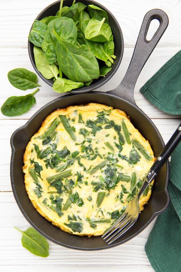 Omlet z szpinakami i fasolkami szparagowymi, zdrowy jedzenie Jajka i mleka Frittata, wy?mienicie ?niadanie W czarnej sma?y niecce obraz stock