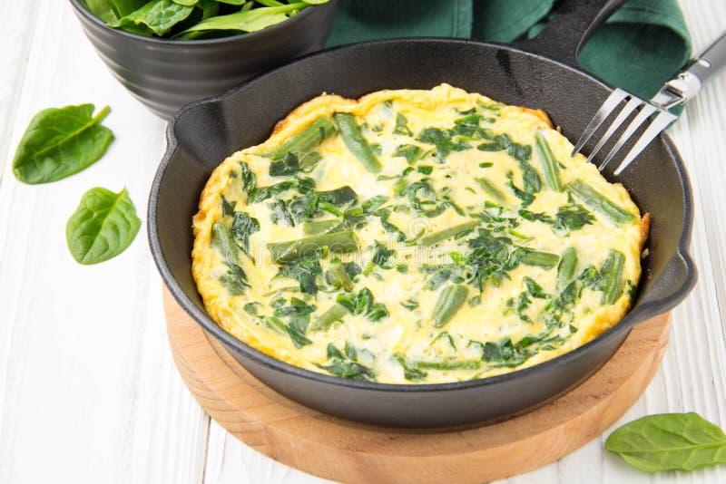 Omlet z szpinakami i fasolkami szparagowymi, zdrowy jedzenie Jajka i mleka Frittata, wy?mienicie ?niadanie W czarnej sma?y niecce zdjęcia stock