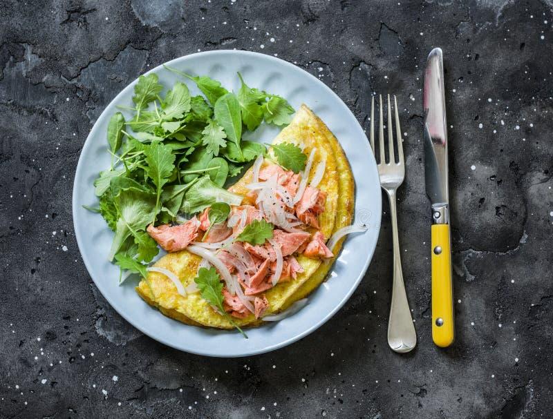 Omlet z zieloną sałatką i piec łososiem na ciemnym tle, odgórny widok Zdrowy ?niadanie, przek?ska fotografia stock