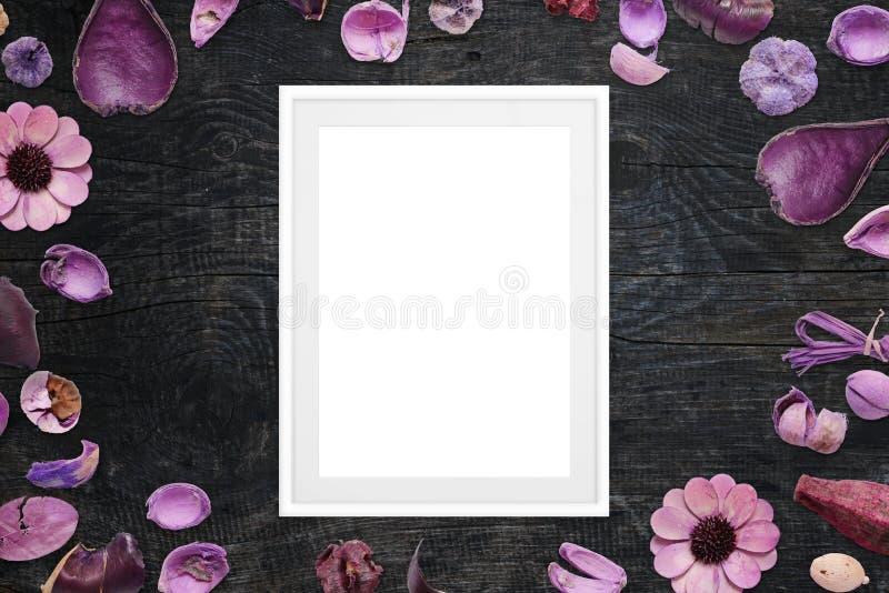Omlijsting op zwart houten die bureau met purpere bloemendecoratie wordt omringd stock fotografie