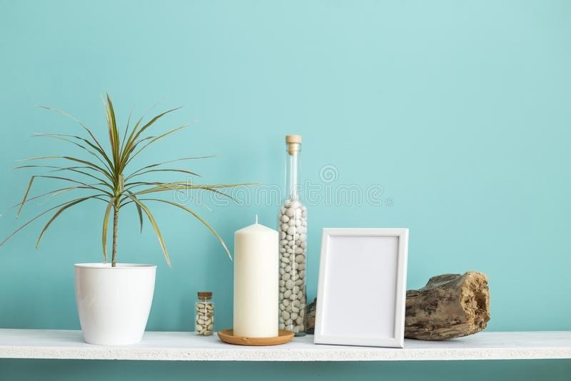 Omlijstingmodel Witte plank tegen pastelkleur turkooise muur met Kaars en rotsen in fles stock foto's