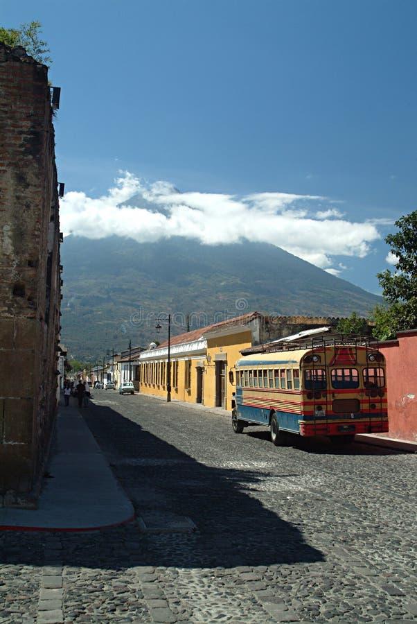 Omnibus y ciudad coloridos delante del volcán fotos de archivo libres de regalías