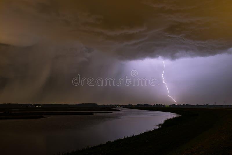 Omnious-Himmel und starker Blitzschlag mit einer Regenwelle links nahe einem See in den Niederlanden stockfoto