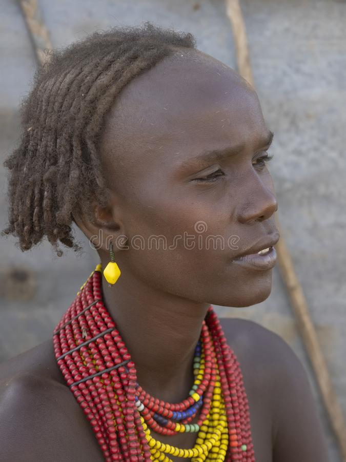 OMO RIVER, ETHIOPIA, MAY 11TH. 2019, Portrait of girl of Dassanech tribe, May 11Th. 2018 dating in Omo river, Ethiopia. Portrait of girl of Dassanech tribe, May royalty free stock photo