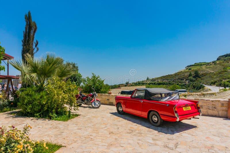 Omodos, Chipre - 7 de junho de 2018: Cena colorida de uma ilha de férias nas montanhas de Troodos Carro vermelho bonito e uma mot imagens de stock