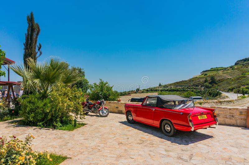 Omodos, Cyprus - June 7, 2018: Colorful scene of a resort island in the Troodos Mountains. Beautiful red car and a red motorcycle stock images