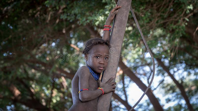 Unidentified girl from Dassanech tribe standing on a branch, Ethiopia. Omorate, Ethiopia - September 2017: Unidentified girl from Dassanech tribe standing on a stock photos