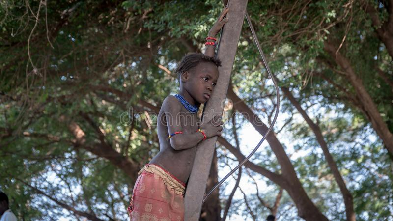 Unidentified girl from Dassanech tribe standing on a branch, Ethiopia. Omorate, Ethiopia - September 2017: Unidentified girl from Dassanech tribe standing on a royalty free stock images