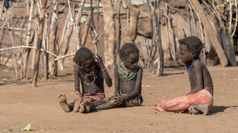Unidentified girls from Dassanech tribe sitting on soil ground , Ethiopia. Omorate, Ethiopia - September 2017: Unidentified girls from Dassanech tribe sitting on stock photography
