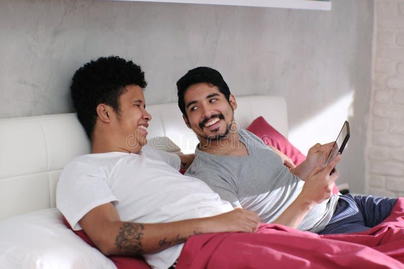 Omosessuale che gioca video con il partner a letto immagine stock libera da diritti