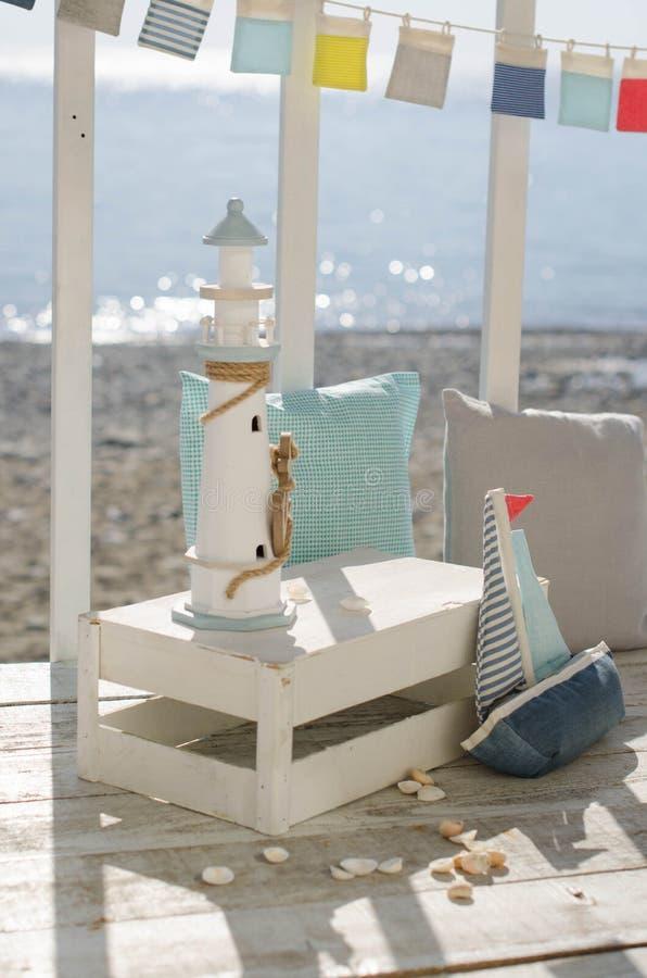 Omposition z plażowymi dekoracji skorupami łódź i latarnia morska, z pillowson fali oceanu tłem zdjęcie stock