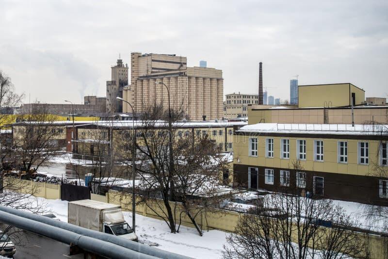 Område av Moskva med växter och lager på en vinterdag industriell arkitektur arkivbild