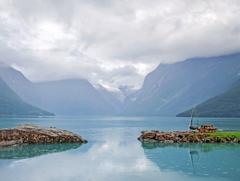 Område för vilar eller har picknick med tabellen och grillar i det sceniska stället nära bergsjön arkivbild