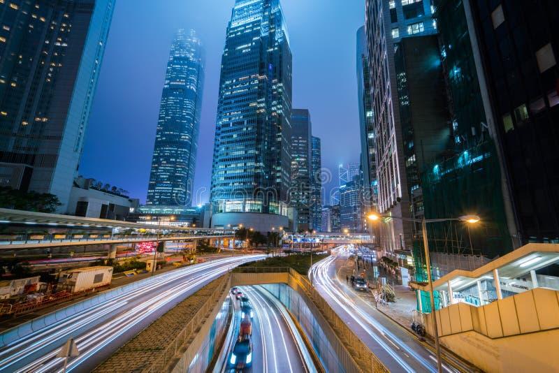 Området för den centrala affären med trafikljus skuggar och det moderna affärstornet på den Hong Kong stadsnatten arkivbild