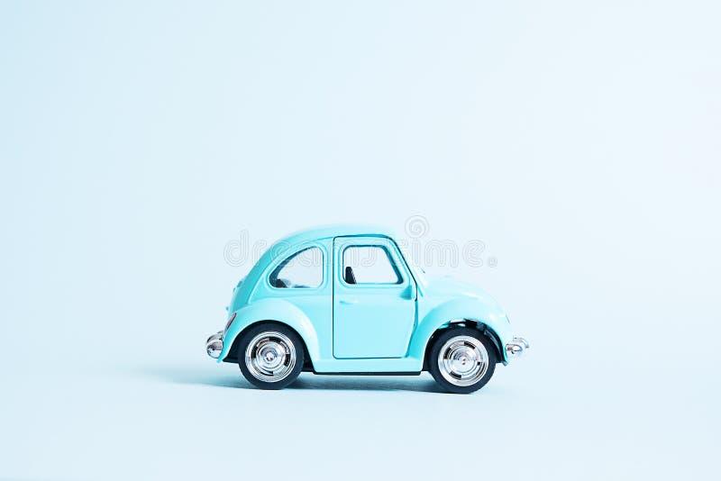 Omsk, R?ssia - 26 de maio de 2019: Carro retro azul do brinquedo no fundo azul Entrega da flor do dia de Valentim 8 de mar?o, con fotografia de stock