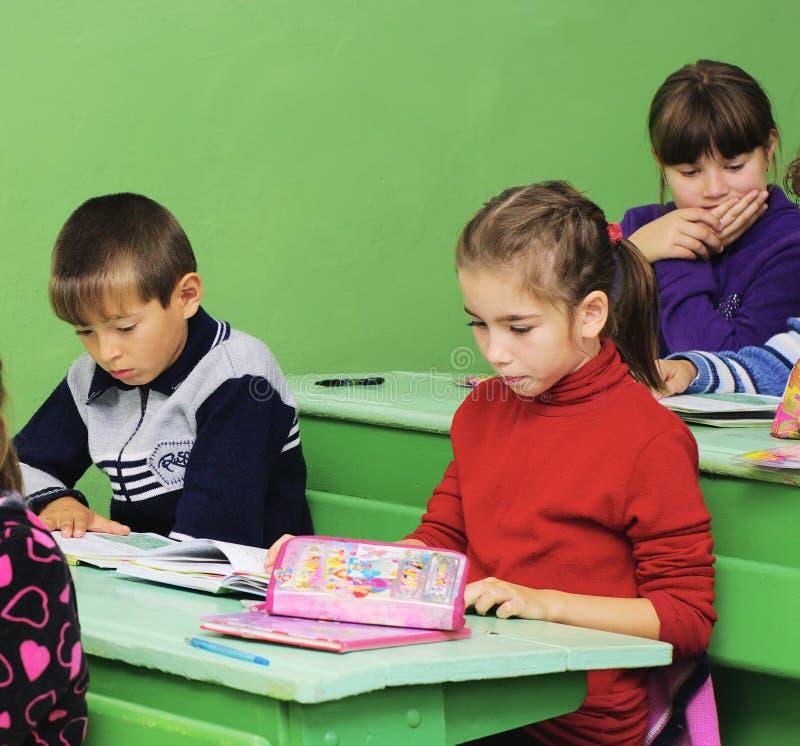 Omsk, Rússia - 24 de setembro de 2011: estudantes da escola primária no close up das mesas da escola fotografia de stock