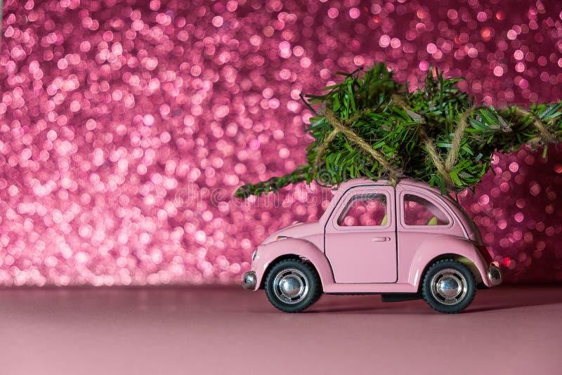 Omsk, Russland - Oktober 27, 2018: Spielzeugmodellauto mit Weihnachtsbaum an auf den Dachfahrten auf rosa unscharfen Funkelnhinte lizenzfreie stockbilder