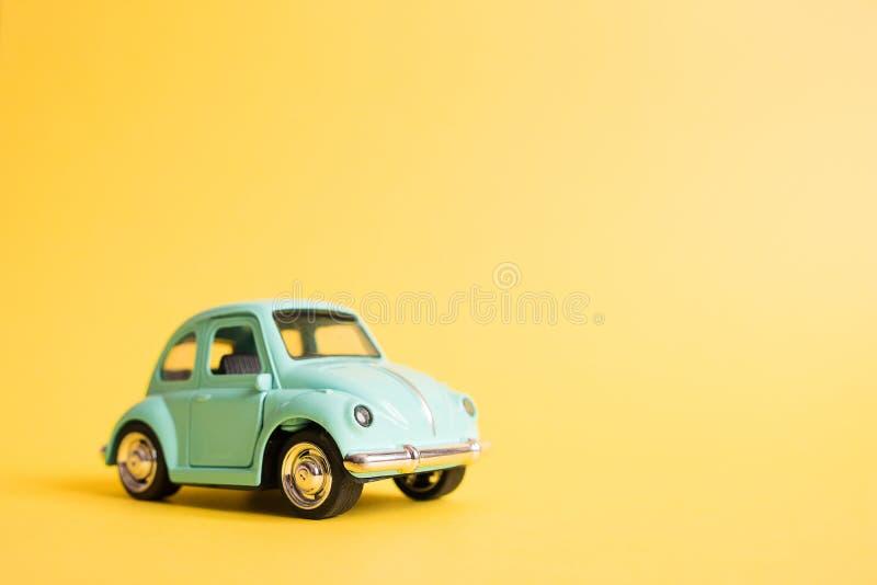 Omsk Ryssland - Maj 26, 2019: Bl? retro leksakbil p? gul bakgrund red steg Loppbegrepp f?r 8 MarchSummer taxa arkivbild