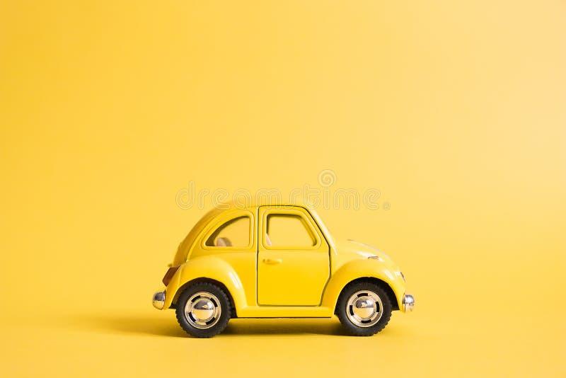 Omsk Ryssland - Maj 26, 2019: Gul retro leksakbil på gul bakgrund red steg kvinnors dag Sommarloppbegrepp taxa arkivbilder