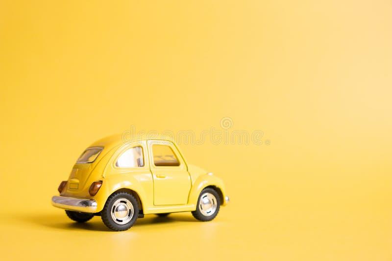 Omsk Ryssland - Maj 26, 2019: Gul retro leksakbil på gul bakgrund red steg kvinnors dag Sommarloppbegrepp taxa fotografering för bildbyråer