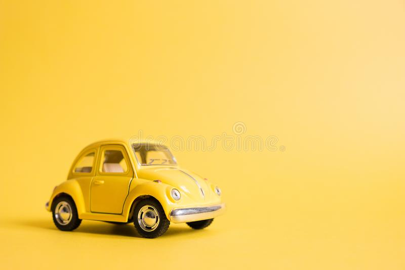 Omsk Ryssland - Maj 26, 2019: Gul retro leksakbil på gul bakgrund red steg kvinnors dag Sommarloppbegrepp taxa royaltyfri foto