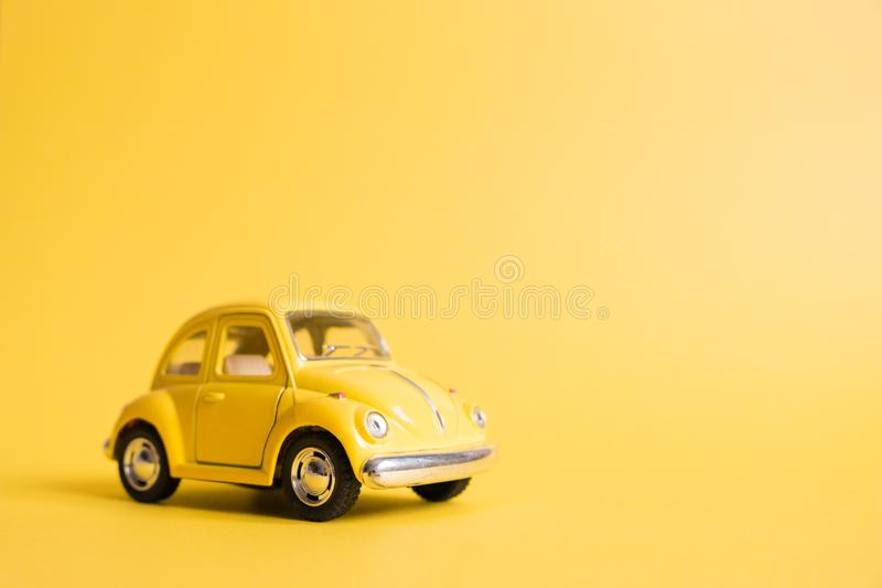 Omsk Ryssland - Maj 26, 2019: Gul retro leksakbil på gul bakgrund red steg kvinnors dag Sommarloppbegrepp taxa arkivfoton