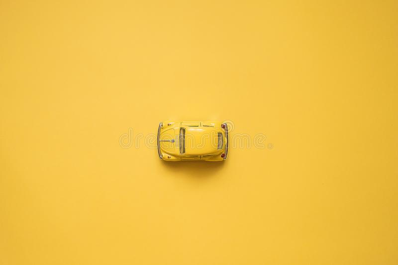 Omsk Ryssland - Maj 26, 2019: Gul retro leksakbil på gul bakgrund red steg Sommarloppbegrepp taxa Top besk?dar arkivbilder