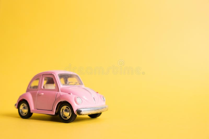 Omsk Ryssland - Maj 26, 2019: Rosa retro leksakbil på gul bakgrund red steg 8 mars Sommarloppbegrepp taxa royaltyfri foto