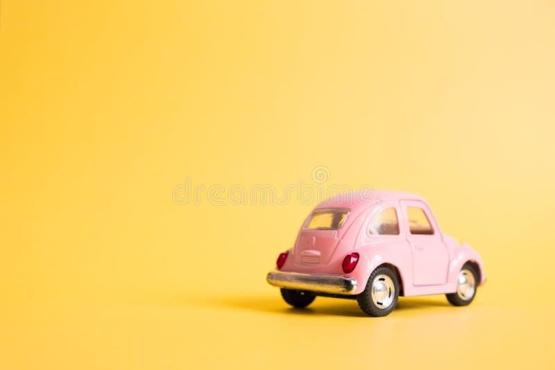 Omsk Ryssland - Maj 26, 2019: Rosa retro leksakbil på gul bakgrund red steg 8 mars Sommarloppbegrepp taxa royaltyfri bild