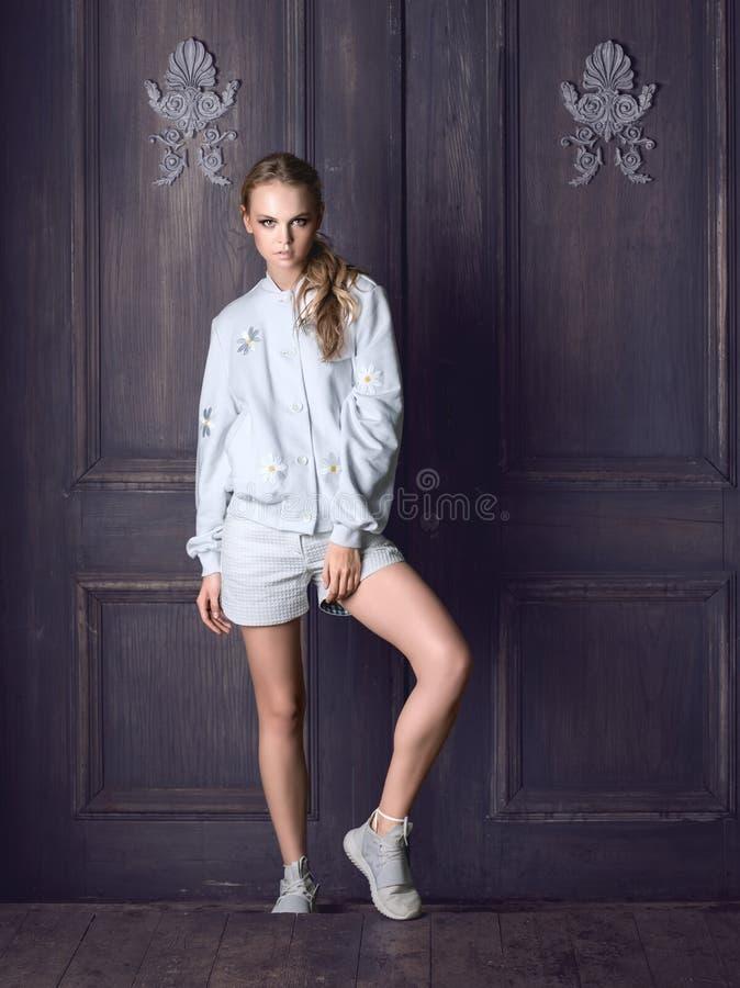 Omslag, kortslutningar och gymnastikskor för modekvinna som bärande vitt poserar mot dörr royaltyfri bild