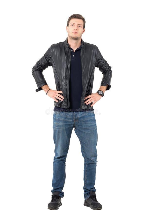 Omslag och jeans för säker stolt tillfällig man bärande med händer på höfter som ser kameran royaltyfri fotografi