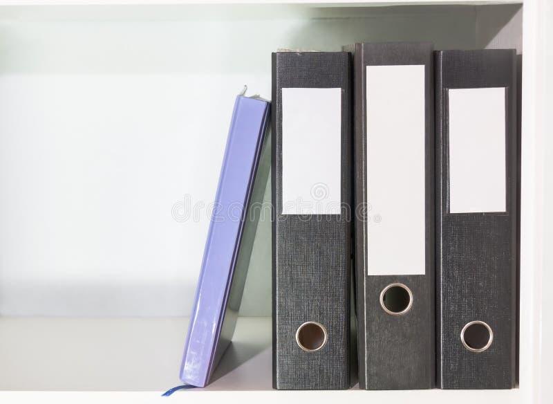 Omslagen voor documenten en ontwerper op een boekenplank royalty-vrije stock foto