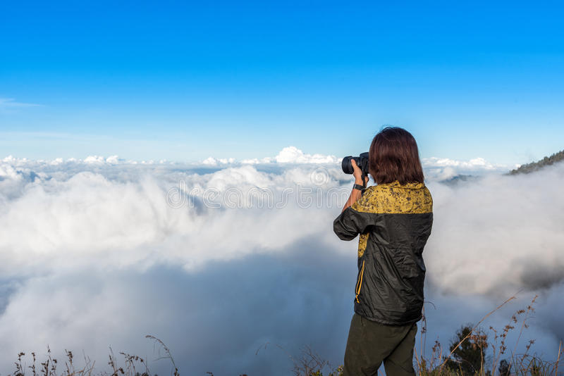 Omslaget för kvinnafotvandrarekläder som tar fotografiet, tycker om och lyckligt med bästa sikt för berg efter färdig klättring p royaltyfria bilder