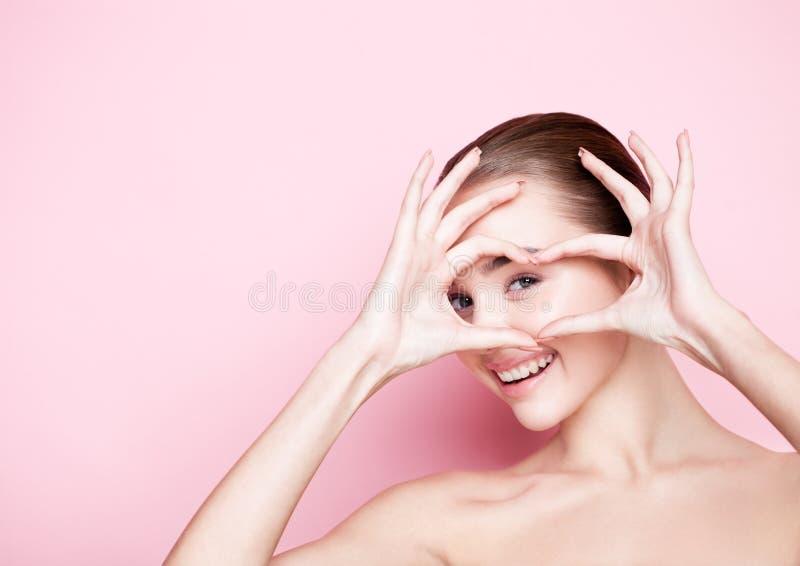 Omsorg för hud för brunnsort för makeup för Beautyl flicka naturlig på rosa färger royaltyfria bilder