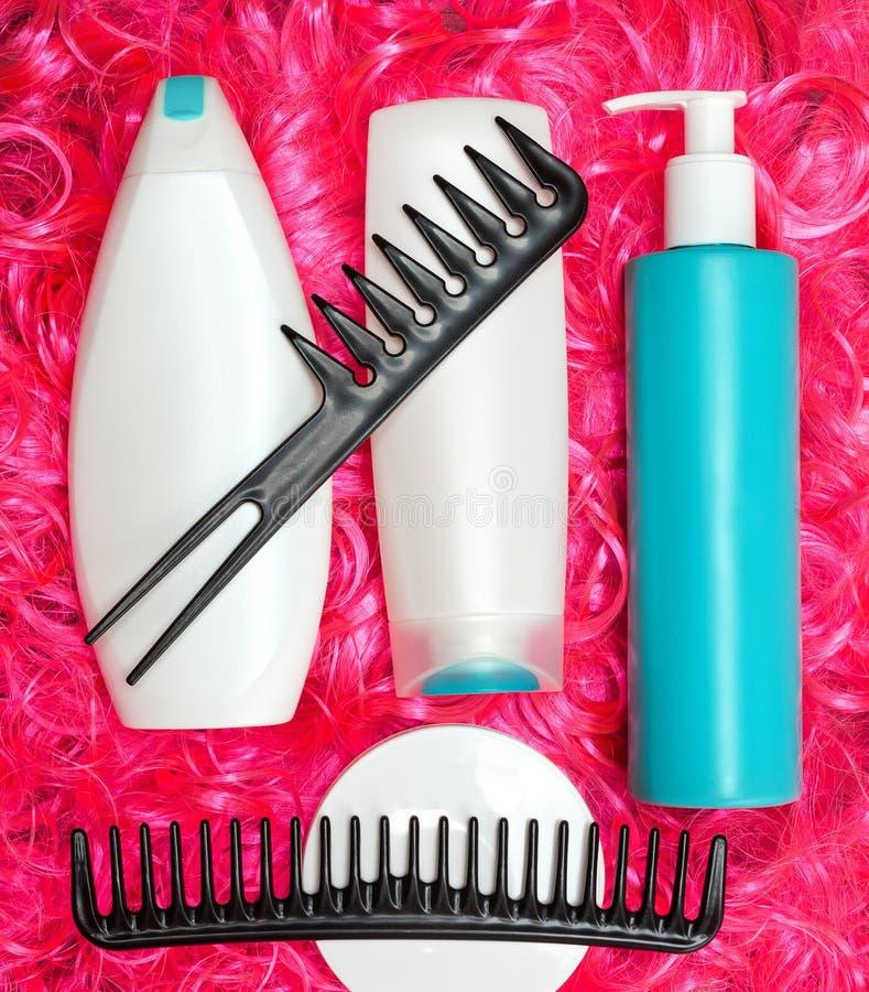 Omsorg för lockigt hår och utformaprodukter på ljust rosa dockahår arkivbilder