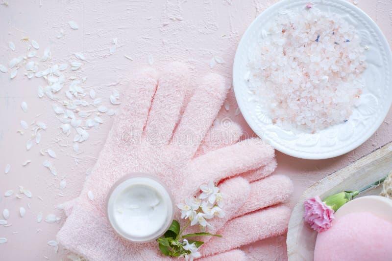 Omsorg, salt hav och handskar för Spa hand Blommorna är vita Rosa bakgrund arkivfoto