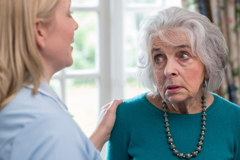 Omsorgarbetare som hemma talar till den deprimerade höga kvinnan royaltyfri foto
