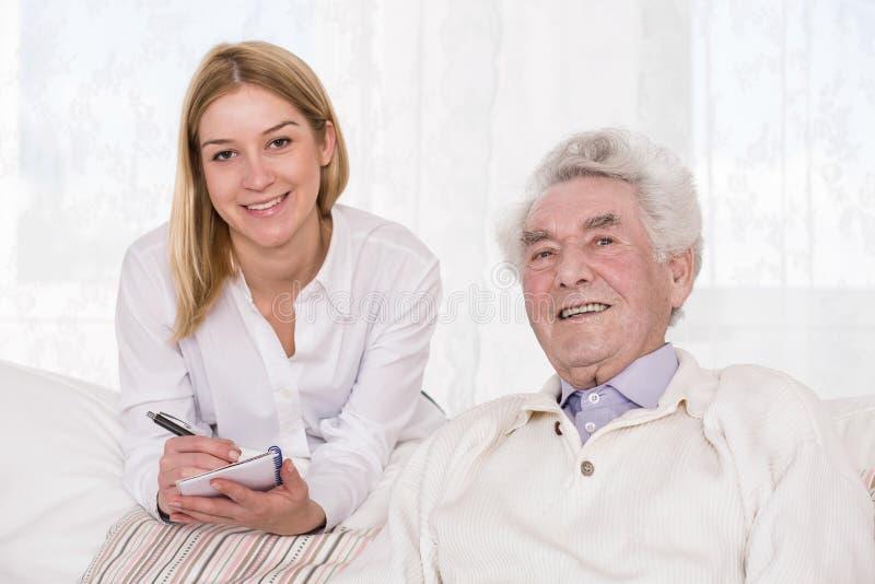 Omsorgassistent och äldre man fotografering för bildbyråer