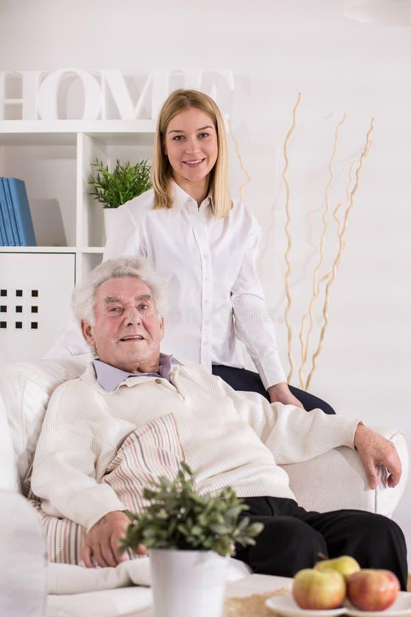 Omsorgassistent och äldre man arkivbild