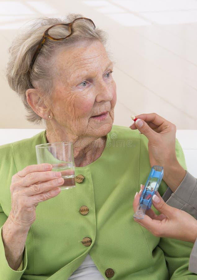 Omsorgdonator eller sjuksköterska som ger till den äldre kvinnan hennes preventivpillerar arkivfoton