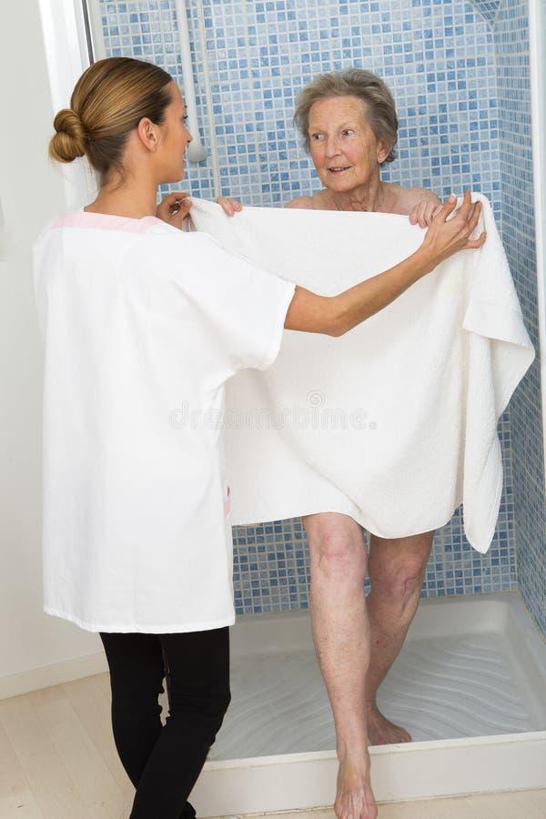 Omsorgdonator eller sjuksköterska som hjälper den äldre kvinnan för dusch royaltyfri foto