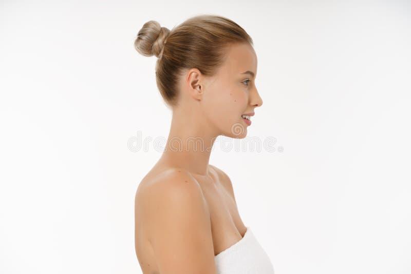 Omsorger för kvinnan för sidosikten vänder mot härliga för huden - posera på studion som isoleras på vit arkivfoto