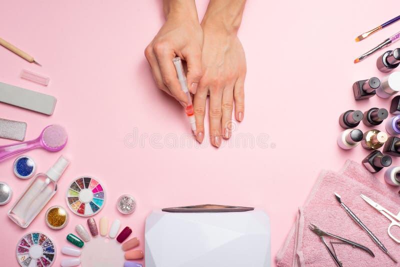omsorgsbomullsfingernailen spikar att ta bort swabfernissa härliga kvinnahänder som framställning spikar målat med rosa försiktig royaltyfri fotografi