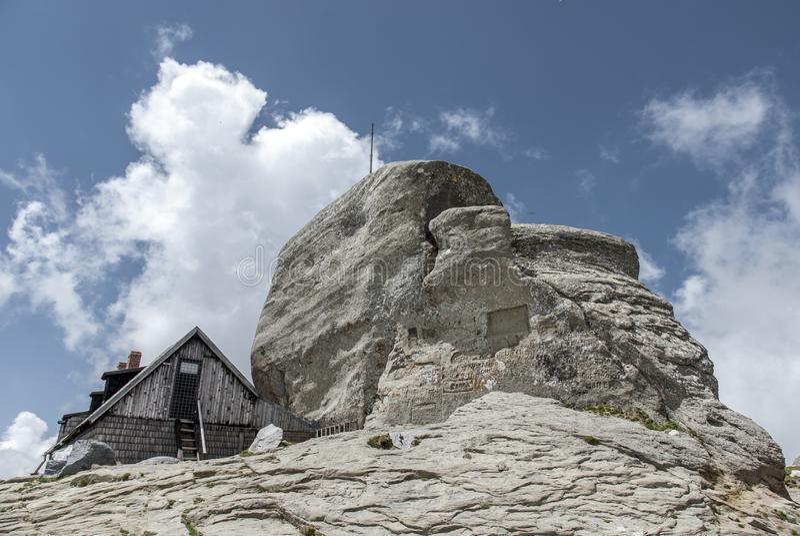 Omu在白色云彩下的峰顶瑞士山中的牧人小屋 库存照片