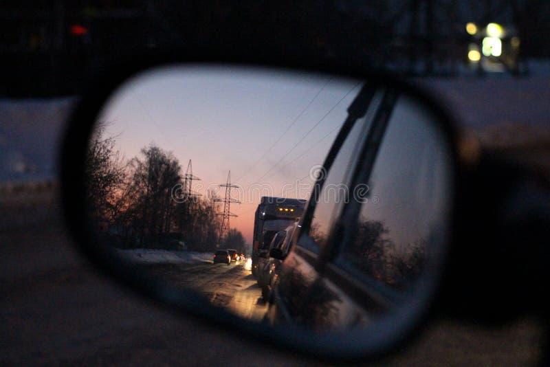 Omvänd reflexion för afton i backspegeln av bilkörning bakom med billyktor på vägen arkivbild