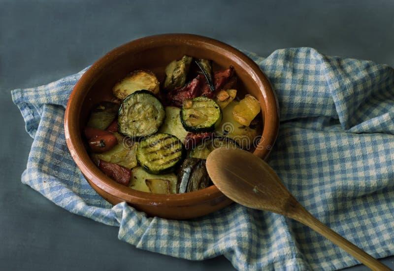 Omväxlande grönsaker som lagas mat i en lerakruka, på ett mörker - grå bakgrund royaltyfri bild